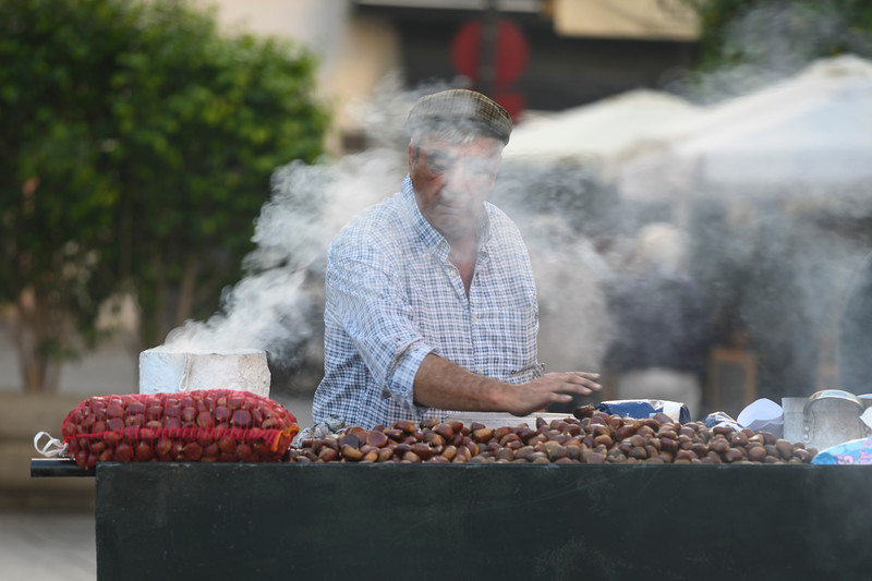 Senior vendor selling roasted chestnuts on the street in Santa Cruz, Seville, Seville Province, Spain