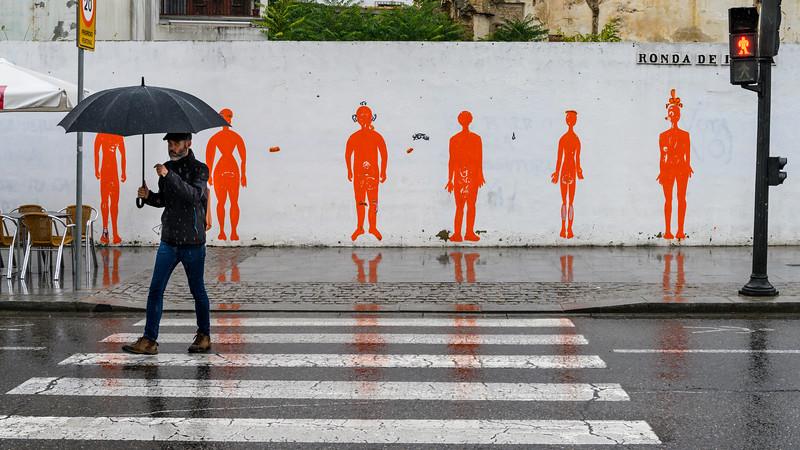 Portrait of a man crossing the road in the rain, Distrito Centro, C�rdoba, C�rdoba Province, Spain