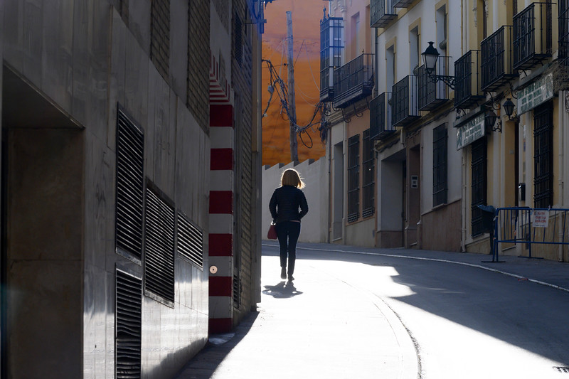 Rear view of woman walking on footpath, Antequera, Andalusia, Spain