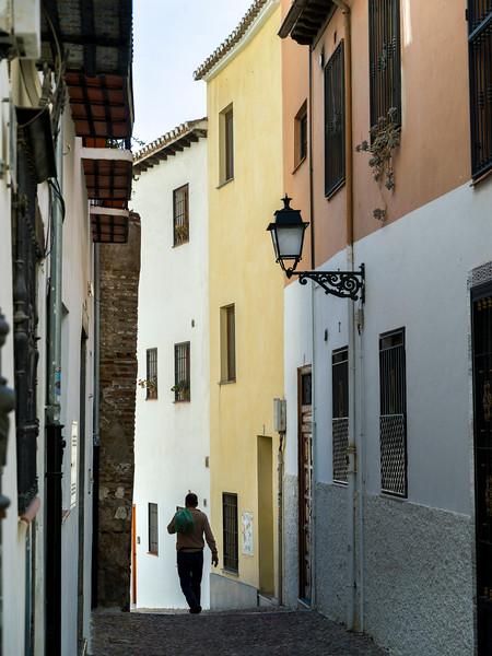 Rear view of a man walking narrow alley of old buildings in town, Granada, Granada Province, Spain