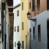 Rear view of a man walking narrow alley of old buildings in town, Granada, Granada Province, Spain