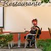 Person wearing a elaborate head wear drinking wine at sidewalk cafe, Santa Cruz, Seville, Seville Province, Spain