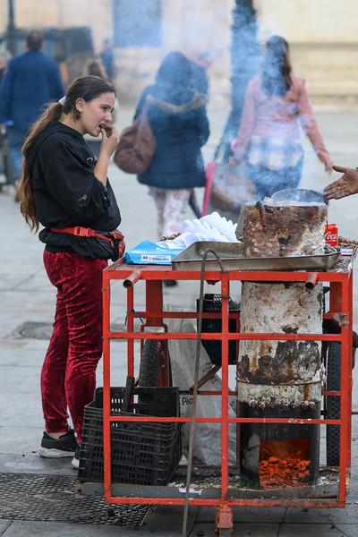 Girl snacking hot chestnuts from a street vendor in Santa Cruz, Seville, Seville Province, Spain