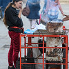 Girl snacking hot chestnuts from a street vendor in Santa Cruz, Seville, Seville Province, Spain