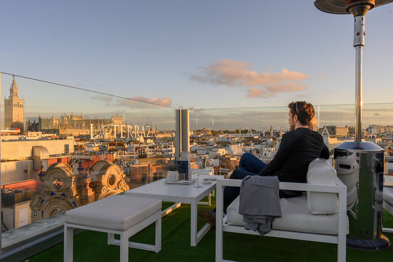 Couple enjoying the view of the historic city from the terrace of La Terraza Hotel in Seville, Seville Province, Spain