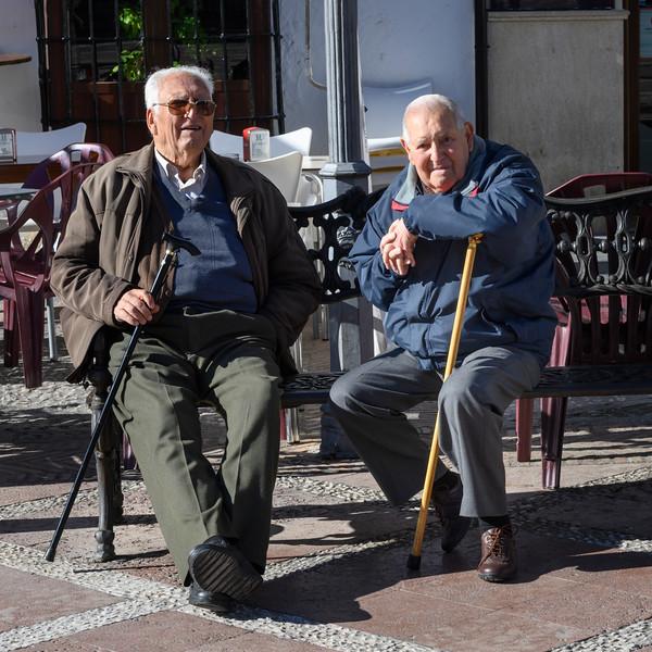 Old male friends sitting on bench, Plaza Del Socorro, Ronda, Malaga, Andalusia, Spain