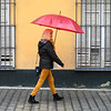 Woman walking on street holding an umbrella, Seville, Seville Province, Spain