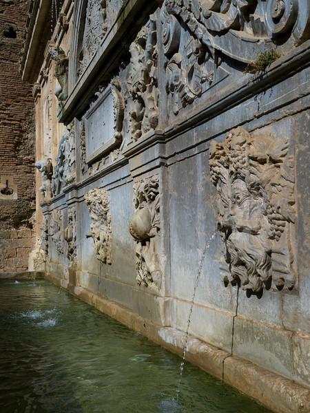 Gargoyle fountain against stone wall of palace, Alhambra, Granada, Spain
