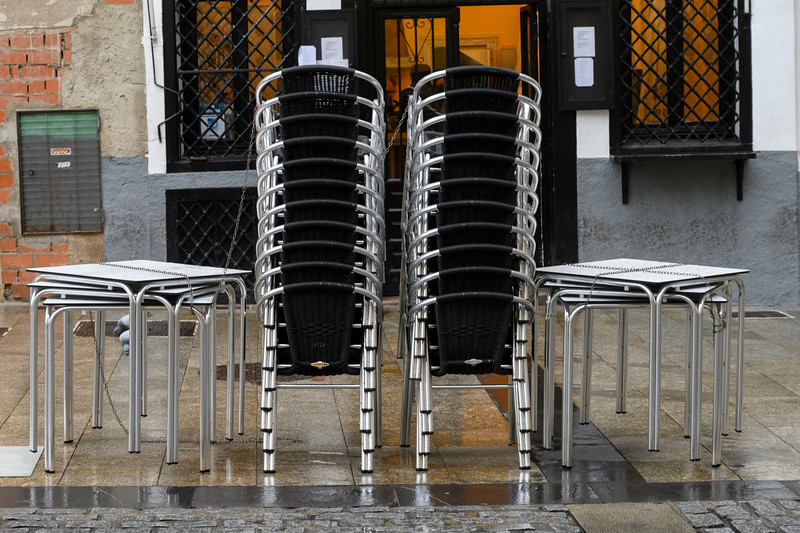 Stacked chairs and tables outside a caf�, Cuenca, Cuenca Province, Castilla La Mancha, Spain
