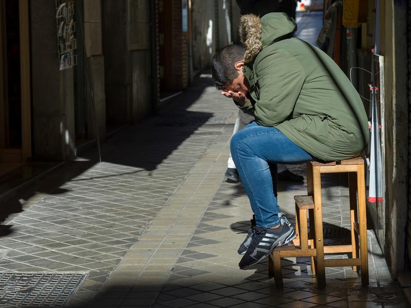 Man relaxing on stool, Granada, Granada Province, Spain