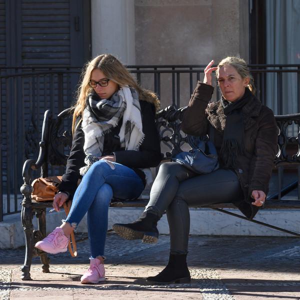 Two women smoking on a bench, Plaza Del Socorro, Ronda, Malaga, Andalusia, Spain