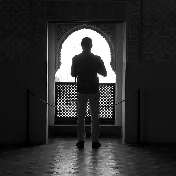 Silhouette of tourist photographing at Nasrid Palaces, Alhambra, Granada, Spain