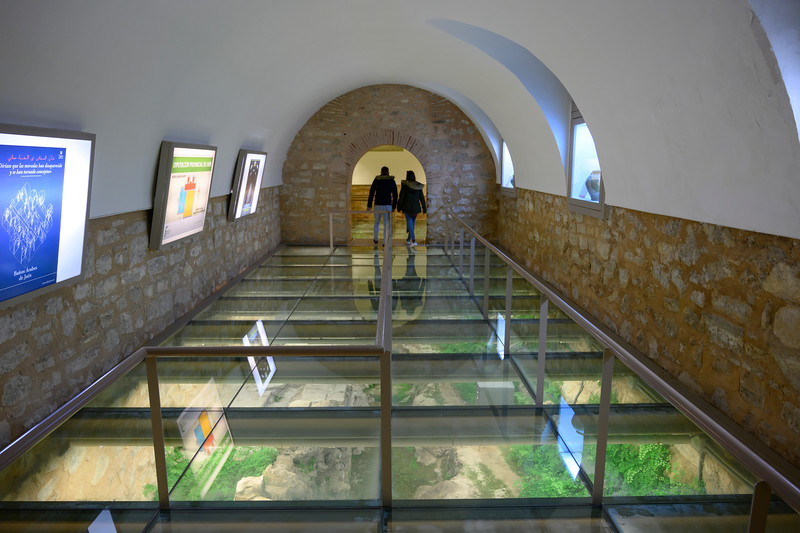 People walking in a corridor with a glass floor, Ubeda, Jaen Province, Spain