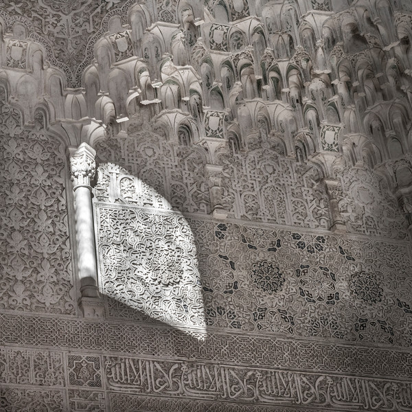 Intricately carved Islamic script on walls of Nasrid Palaces, Alhambra, Granada, Spain