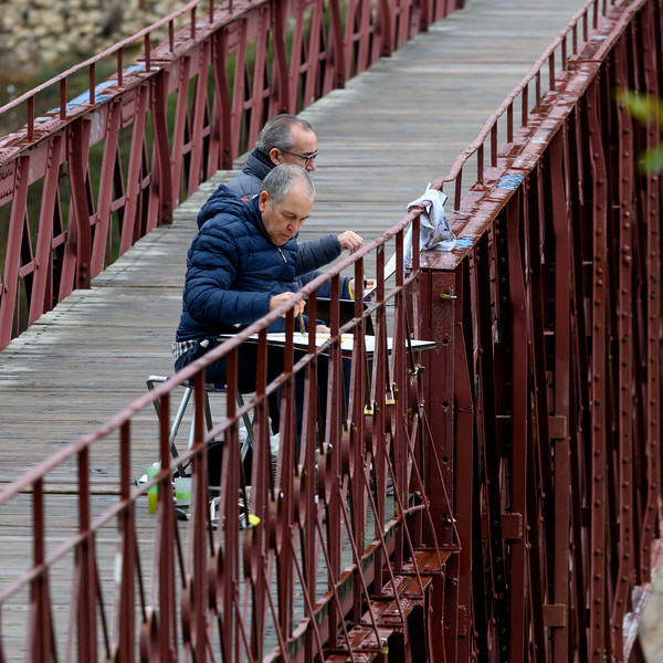 Two senior artists painting on canvas while sitting on San Pablo Bridge, Cuenca, Spain
