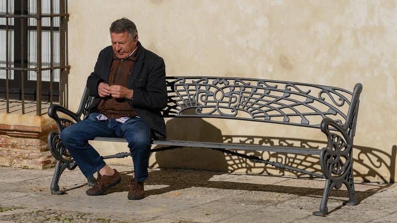 Senior man sitting on bench, Ronda, Malaga, Andalusia, Spain