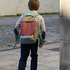Rear view of boy with a backpack walking, Spain