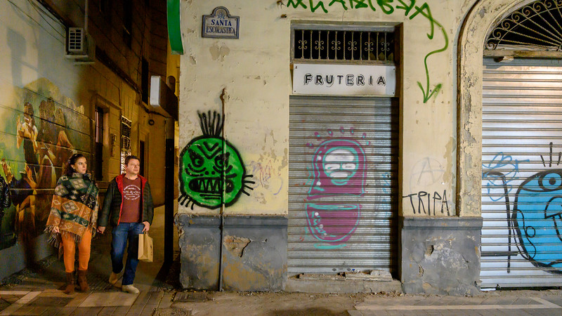 Couple walking in alley with graffiti on walls, Albolote, Granada Province, Spain