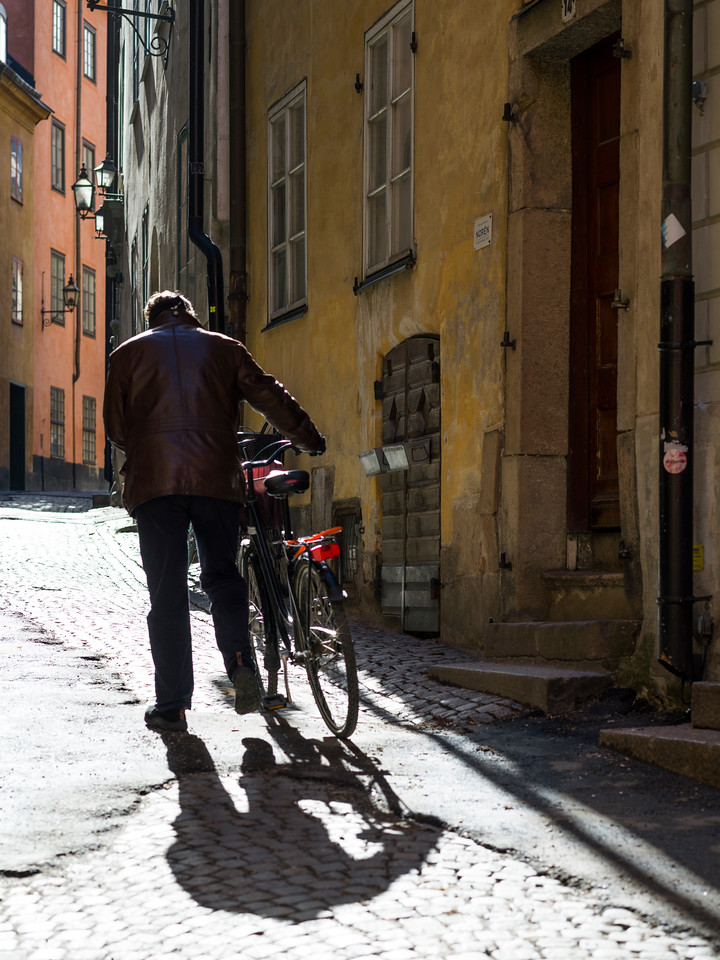 Man walking with bicycle in street, Gamla Stan, Stockholm, Sweden