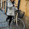 Woman walking with bicycle in street, Gamla Stan, Stockholm, Sweden