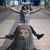 Happy woman sitting on lion sculpture, Drottninggatan Street, Stockholm, Sweden