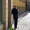 Rear view of man standing on sidewalk, Gamla Stan, Stockholm, Sweden
