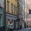 Woman standing with bicycle in street, Gamla Stan, Stockholm, Sweden