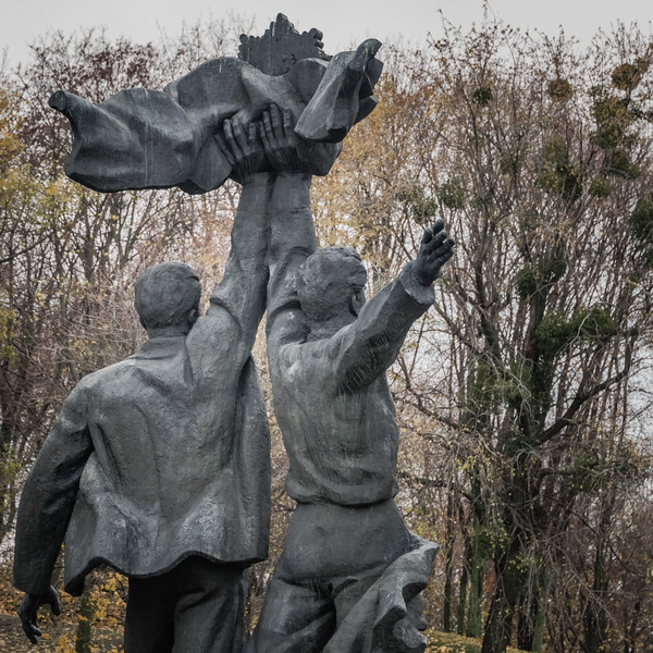 Russian and Ukrainian workers holding up the Soviet Order of Friendship of Peoples under the Friendship of Nations Arch