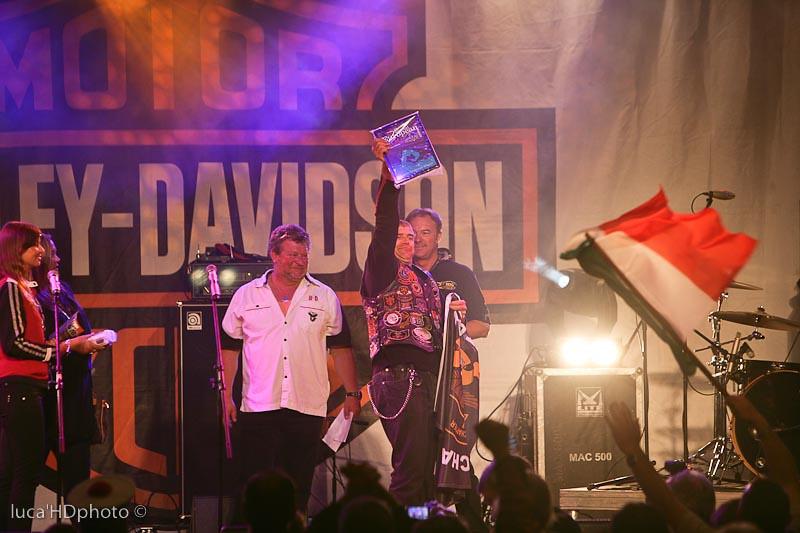 Il Director del Verona Chapter premiato da Nigel Villiers e Claudio De Negri, sotto il palco gli italiani con il tricolore esultano.