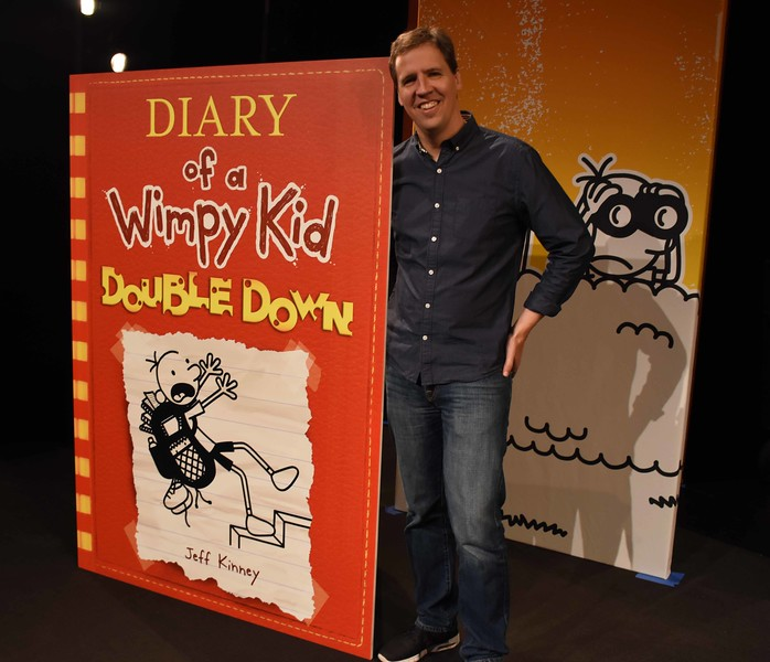 Jeff Kinney, author of the Wimpy Kid Series, poses with the cover of the new book, Diary of a Wimpy Kid Double Down, at the cover reveal, on April 28, 2016, in New York City.