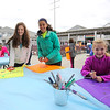 (L to R) JR Miss Hampton Beach Maeve Hess with friend Noelia Mason and Little Miss Hampton Beach Rowan Hess work on decorating their kites  at Sunday's Kites Against Cancer benefit for Exeter Hospital's Beyond the Rainbow Fund at a windy Hampton Beach on 5-15-2016.  Matt Parker Photos