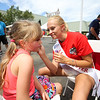 Miss Exeter Samantha Mackes paints the face of Barringtons' Kaiya Mercier at Sunday's Seacoast Salutes Military Appreciation Day sponsored by Seacoast Service Credit Union, Redhook Brewery and others on 7-24-2016, Redhook Brewery, Portsmouth, NH.  Matt Parker Photos