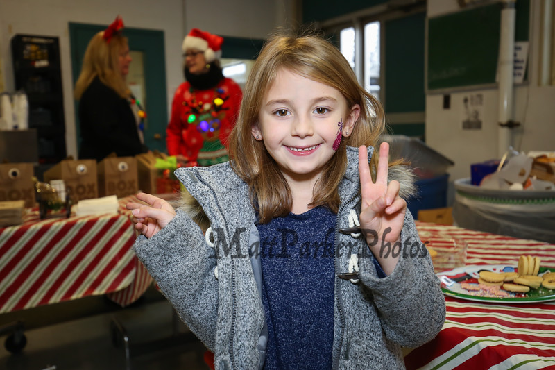 Maya Beaulieu and her big smile gives us a peace sign with the hope that her older sister Meg Dzialo will soon be home for Christmas break from Merrimack College (where she is studying hard) at the 2017 Annual Hampton PTA Breakfast with Santa on Saturday @ Hampton Academy on 12-9-2017.  Matt Parker Photos