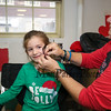 "2nd grader Ally Salvia gets a festive temporary tatoo by Doreen Doddy of ""Doddy Dots"" at the 2017 Annual Hampton PTA Breakfast with Santa on Saturday @ Hampton Academy on 12-9-2017.  Matt Parker Photos"