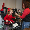 "preschooler Lia Spinelli looks in the mirror at the temporary ""Peace""  tatoo on her cheek applied by Doreen Doddy of ""Doddy Dots"" at the 2017 Annual Hampton PTA Breakfast with Santa on Saturday @ Hampton Academy on 12-9-2017.  Matt Parker Photos"