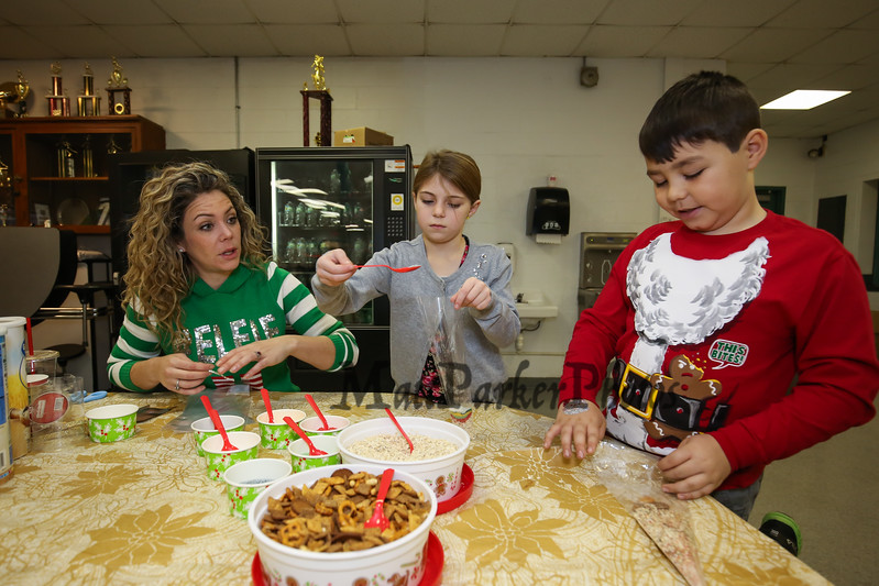 """Elfie"" helps 2nd graders Ella O'Brien and Nolan Durant make a bag of, ""reindeer food"" at the 2017 Annual Hampton PTA Breakfast with Santa on Saturday @ Hampton Academy on 12-9-2017.  Matt Parker Photos"