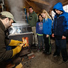 "Maple sugar house operator and 4th grade teacher Jim Cutting feeds pine wood to the evaporator while (L to R) Scott Elzey with 4th graders Maya Tanida, Elizabeth Medford and Miguel Gherfi look on at the Lincoln Akerman School 4th grade ""Sugaring-Off"" Maple Syrup Party on Saturday 3-25-2017 @ Hampton Falls, NH.  Matt Parker Photos"