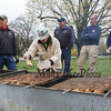 Jennifer Gingras puts seasoning on the BBQ Chicken as members of the Hampton Falls FD and PD look on at the 2017 Earth Day Jam and Chicken BBQ with Friends of the Hampton Falls Bandstand on Saturday 4-22-2017 @ Hampton Falls Fire Department, NH.  Matt Parker Photos