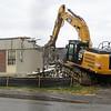 A Cat 336E excavator removes the walls of the 6th grade addition at the Hampton Academy Groundbreaking-reconstruction ceremony on a rainy Monday 7-24-2017, Hampton, NH.  Matt Parker Photos
