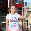 4th grader Maeve Paige poses next to a fire truck at the Exeter Police and Fire Department Open House at the Exeter Safety Complex on Saturday 9-23-2017 @ Exeter, NH.  Matt Parker Photos