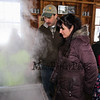 "LAS teacher and Sap Man Jim Cutting explains the maple syrup process to Allie King with daughter Xenia at the Lincoln Akerman School 4th grade annual Sugaring Off Maple Syrup Party on Saturday 3-17-2018 @ the, ""LAS Sugar Shack"", Hampton Falls, NH.  Matt Parker Phtotos"