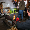 """Scott Elzey stokes the fire for the evaporator with hot burning split pine fuel at the Lincoln Akerman School 4th grade annual Sugaring Off Maple Syrup Party on Saturday 3-17-2018 @ the, """"LAS Sugar Shack"""", Hampton Falls, NH.  Matt Parker Phtotos"""