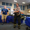 Student Daniel Melican Jr. (L) uses a stopwatch where he timed Pete Robie on how fast he put on his firefighting gear at his booth where his fire fighting gear was on display for his  ELO in Firefighting under-Hampton Fire/Rescue & Seabrook Fire Departments at the Winnacunnet High School ELO (Extended Learning Opportunities) Exhibition Night on Thursday 5-3-2018 @ WHS cafeteria, Hampton, NH.  Matt Parker Photos