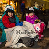 Newton residents 4th grader Collin Corriveau with his 2nd grade sister Katelyn with front row seating as they makes themselves comfortable in the freezing weather at the 62nd Annual Exeter Holiday Parade on Saturday Night 12-7-2019, Exeter NH.  [Matt Parker/Seacoastonline]