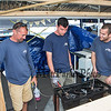 Owner Kevin Hart (L) of Hart Plumbing has been hooking up gas lines to the food booths for the past 19 years, here he works with son Hunter Hart (M) and Sam Reid (R) testing the gas stoves at the 30th Annual Hampton Beach Seafood Festival, setting up the food booths on Thursday 9-5-2019 @ Hampton Beach, NH.  Matt Parker Photos