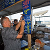 Rocky Anzalone of the Boston Chowder Co. drives a nail into a 2x4 holding up his menu signs at their food booth, 30th Annual Hampton Beach Seafood Festival, setting up the food booths on Thursday 9-5-2019 @ Hampton Beach, NH.  Matt Parker Photos