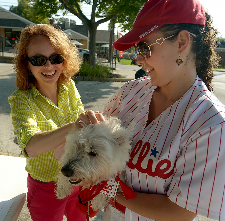 . Mayor Jeanne Sorg, left, ruffles Dante\'s fur after pinning on the West Highland terrier\'s registration number for the Ambler Dog Days Parade Saturday, Aug. 9, 2014. Dante belongs to Marilee Gallagher. Montgomery Media staff photo by Bob Raines