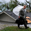 Kelly Molher walks by a roof lying on the ground as he leaves Swan Creek trailer park carrying a few belongings after a tornado hit the community in Limestone County, Ala. Wednesday, April 27, 2011.