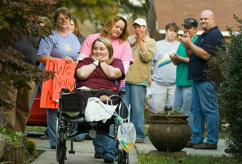 Polly Moses pushes her daughter Molly's wheelchair up the new ramp built outside their house as friends and relatives give Molly a big applause Monday, November 16, 2009, when she came home for the first time after spending 108 days at the hospital. A boating accident on July 31 almost severed Molly Moses' left leg, left her with deep gashes and broke bones in her right leg and hip. Doctors, who said they were amazed she survived, had to amputate her left leg.