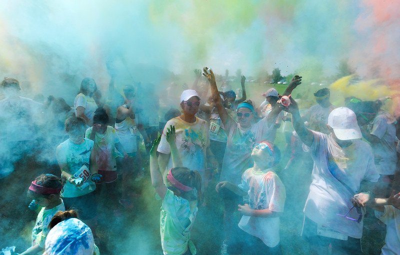 """Participants in the """"Color Your World"""" 5K run at Oakville Indian Mounds Park cheer in a cloud of colored powder at the end of the run Saturday, June 8, 2013. The event, organized by Mount View Baptist Church, raised funds for an International Mission Team to go to Nicaragua."""